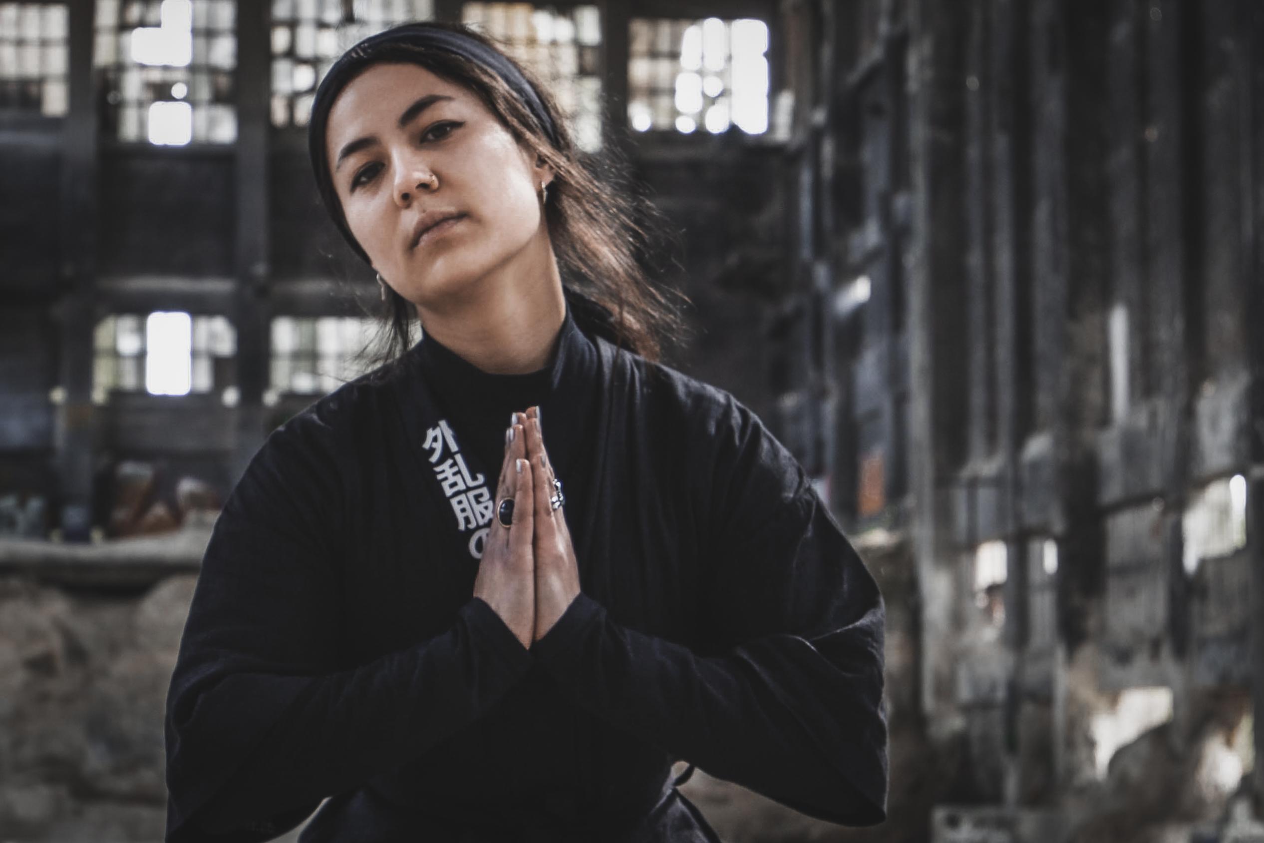 Eine junge Frau steht in einer Industriehalle und hält ihre Hände zum Gebet.