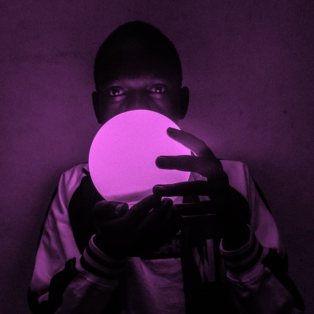 man with light ball and pink background