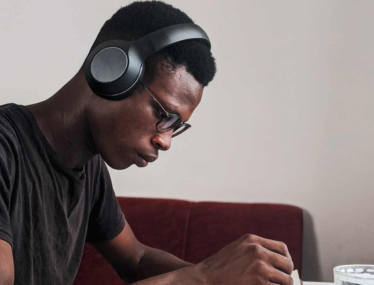 A black man listening along while reading a book