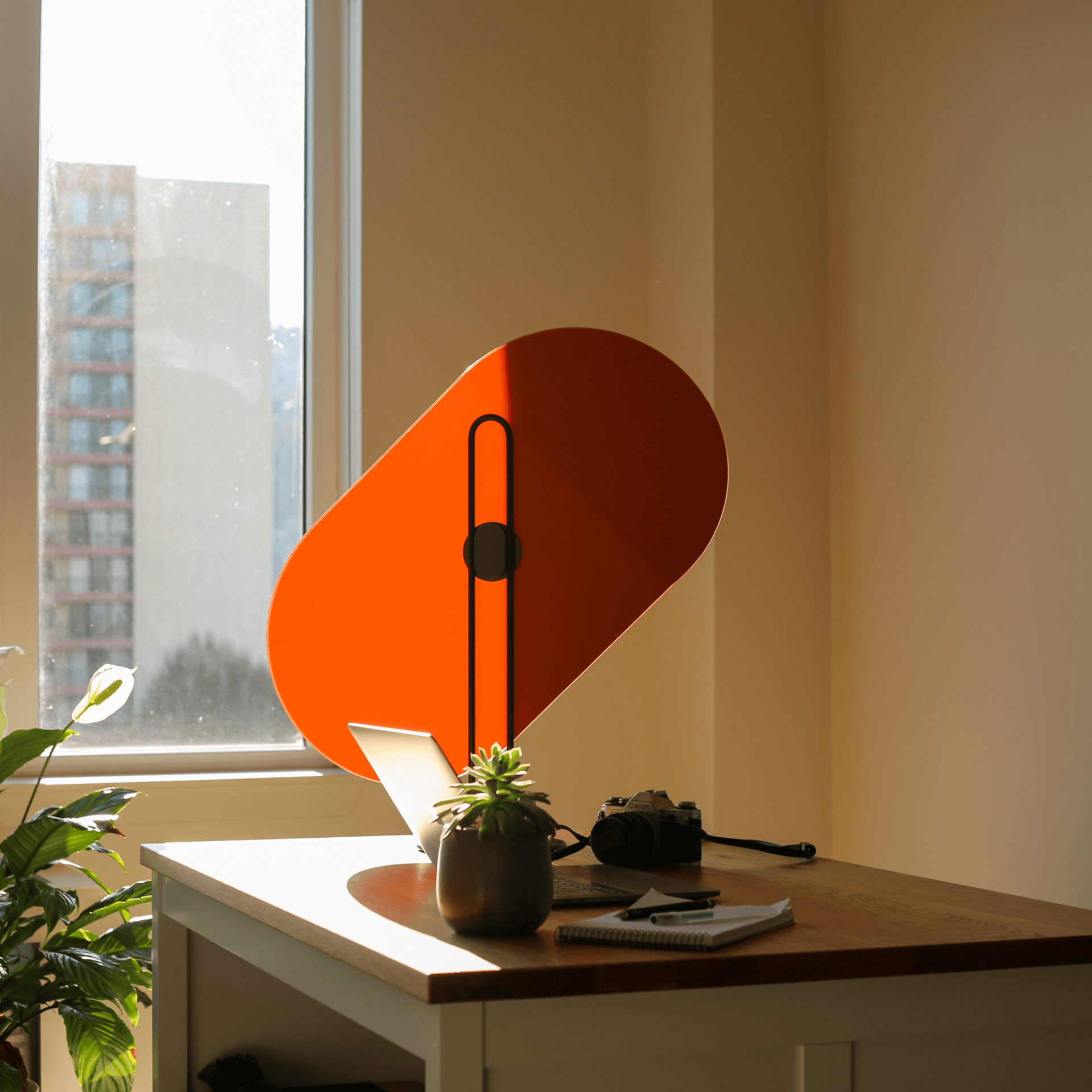 A relaxing photo of an orange Taskshade in a home office. The light warms and glows on half the shade.