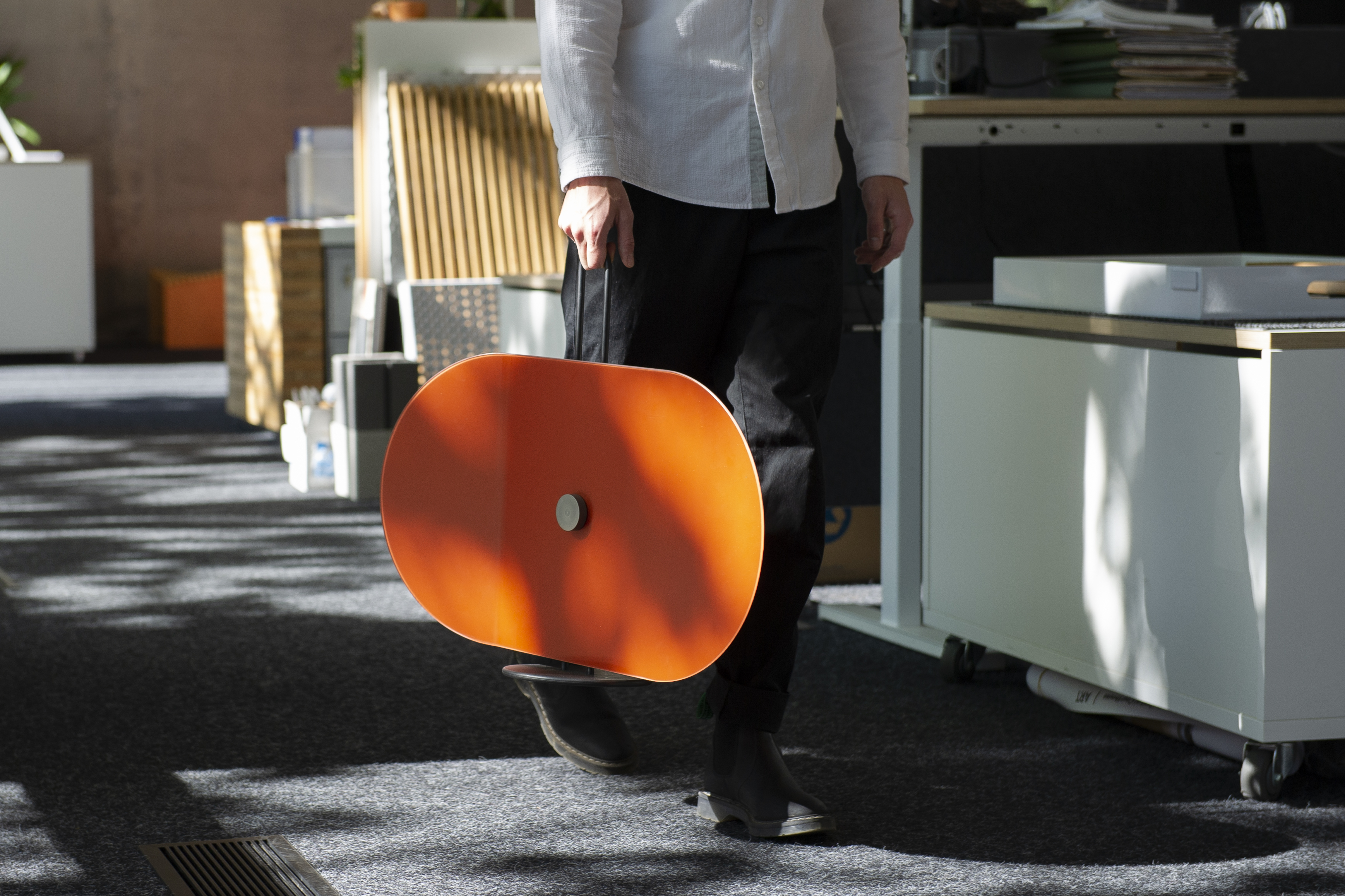 Office worker carrying an orange Taskshade while they walk down a daylit hallway.