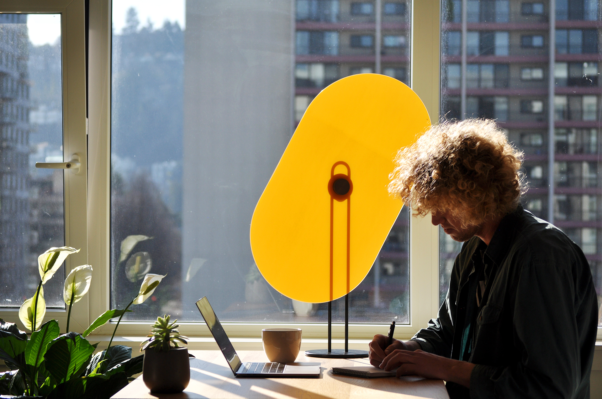 A curly-haired Peter sketching in his notepad by a window. Taskshade shading his work.
