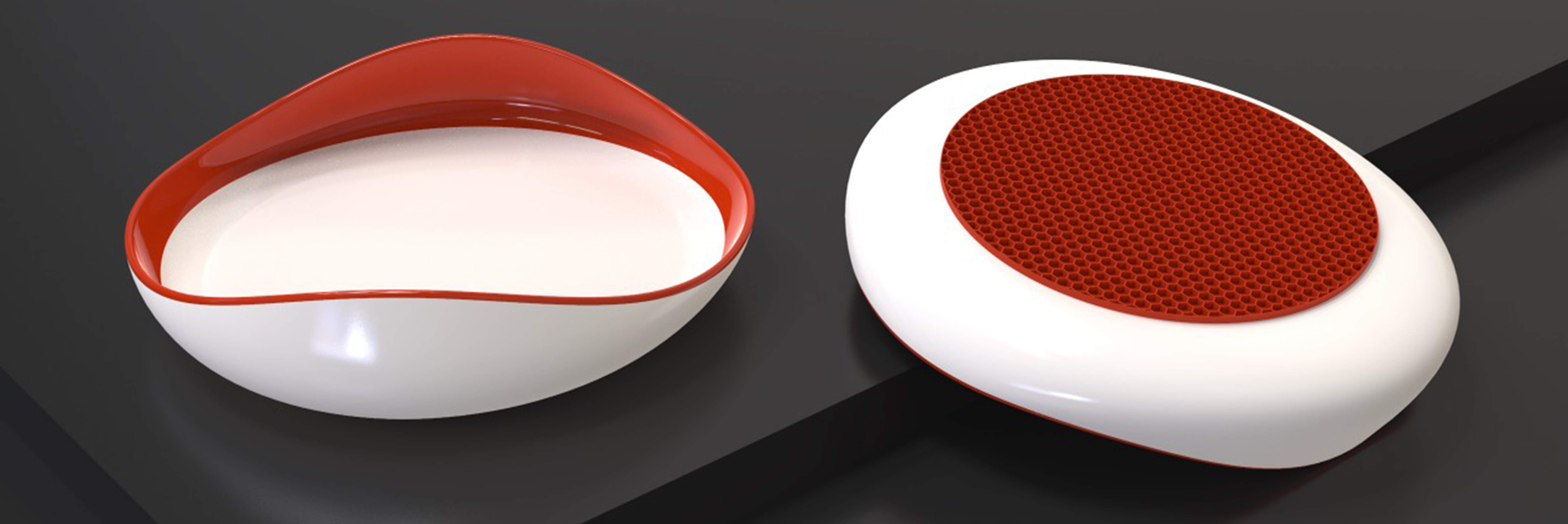 A rendering of two of the same cream coloured, irregularly shaped dishes with red accents on a black background. The dish on the left shows that the product has higher edges on two of its four sides, sloping inward, and painted with a red interior. The dish on the right shows a red patterned silicone bottom on the dish.