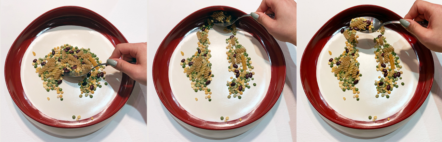 In context image of final design in use. Top view of dry food being pushed to one plate edge, loading the food onto the spoon for the user.