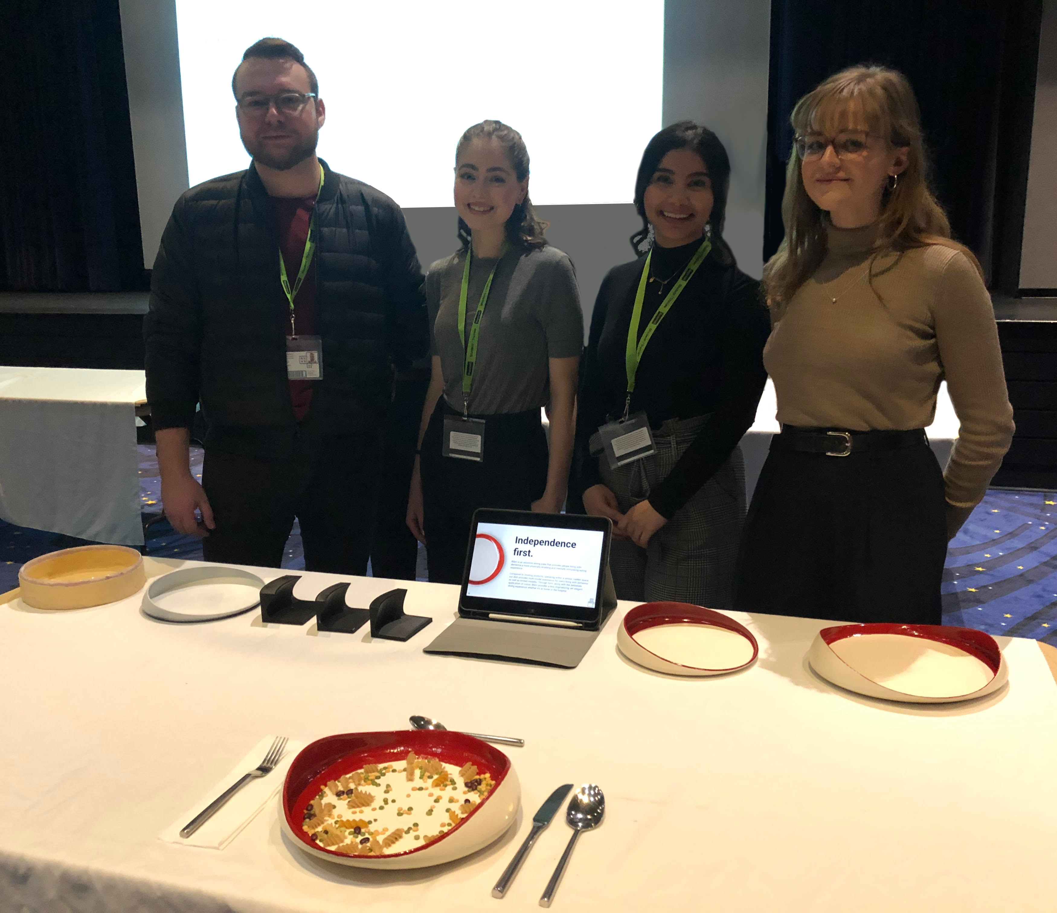 Photograph of design team standing behind prototypes from different stages in the design process as well as the final design staged with utensils and food.
