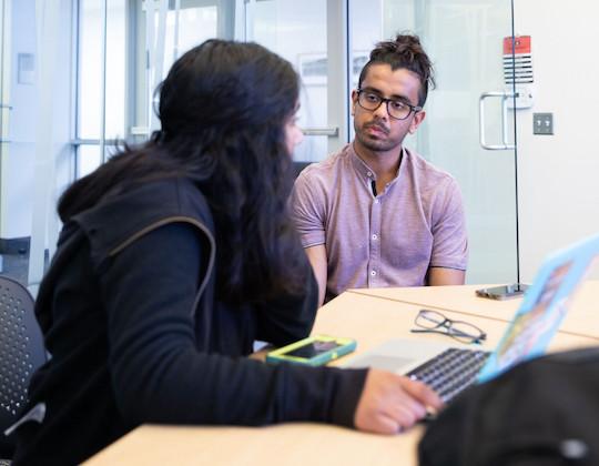 DebateDrills Founder Paras Kumar tutors a student at a tournament.