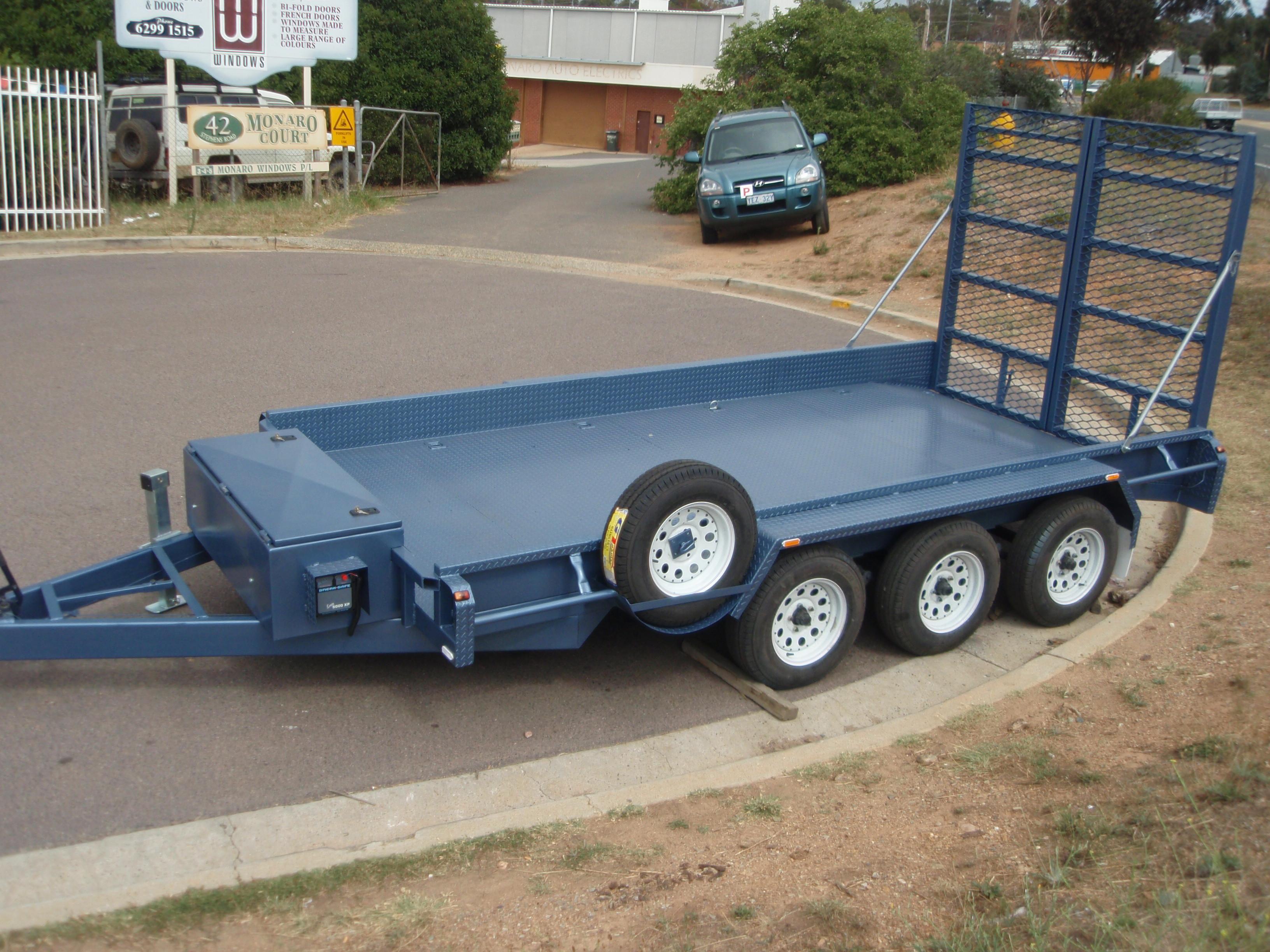 Large, blue car trailer, triple axle.