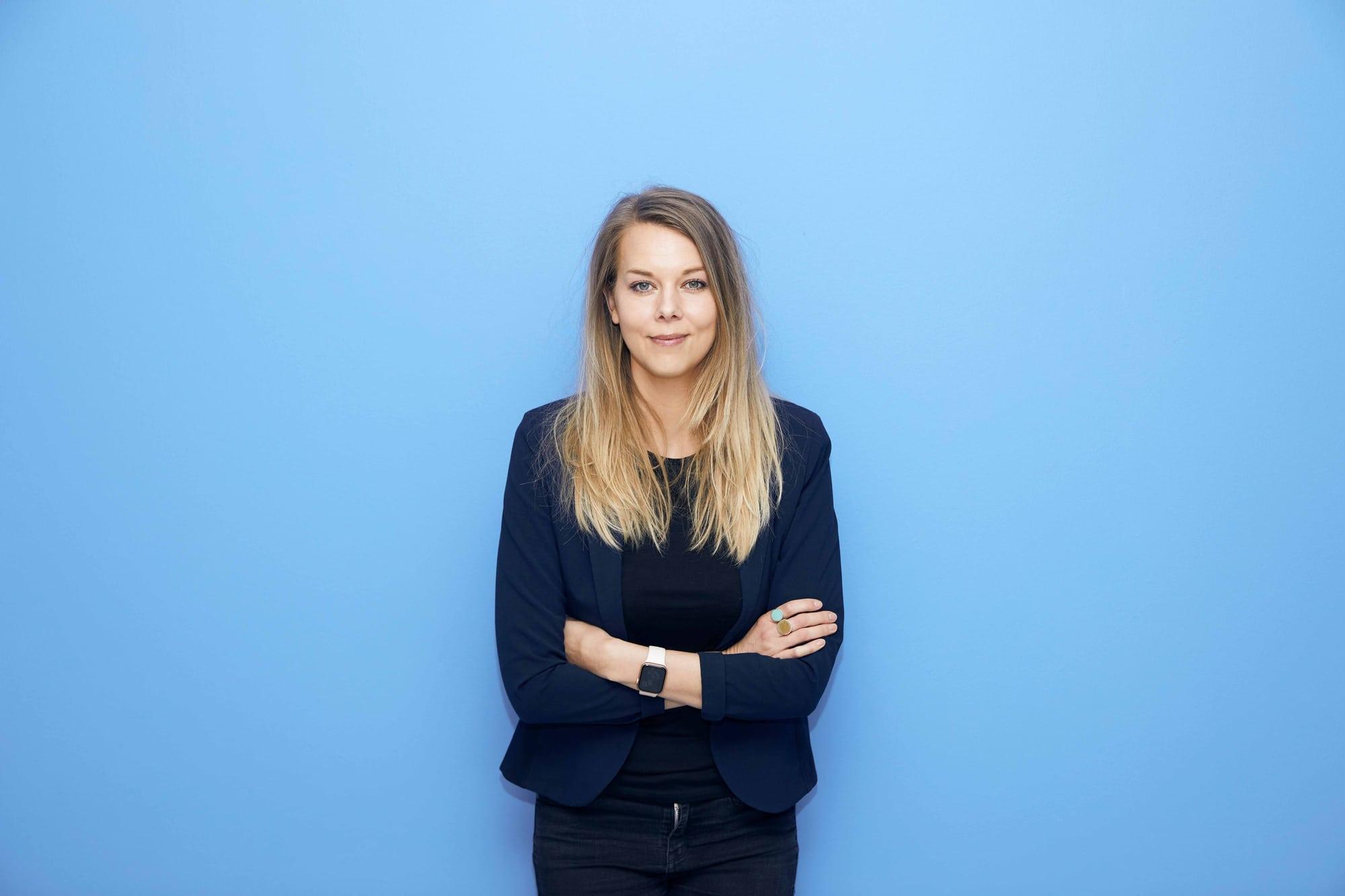 Et billede af Signe Daugaard foran en blå væg