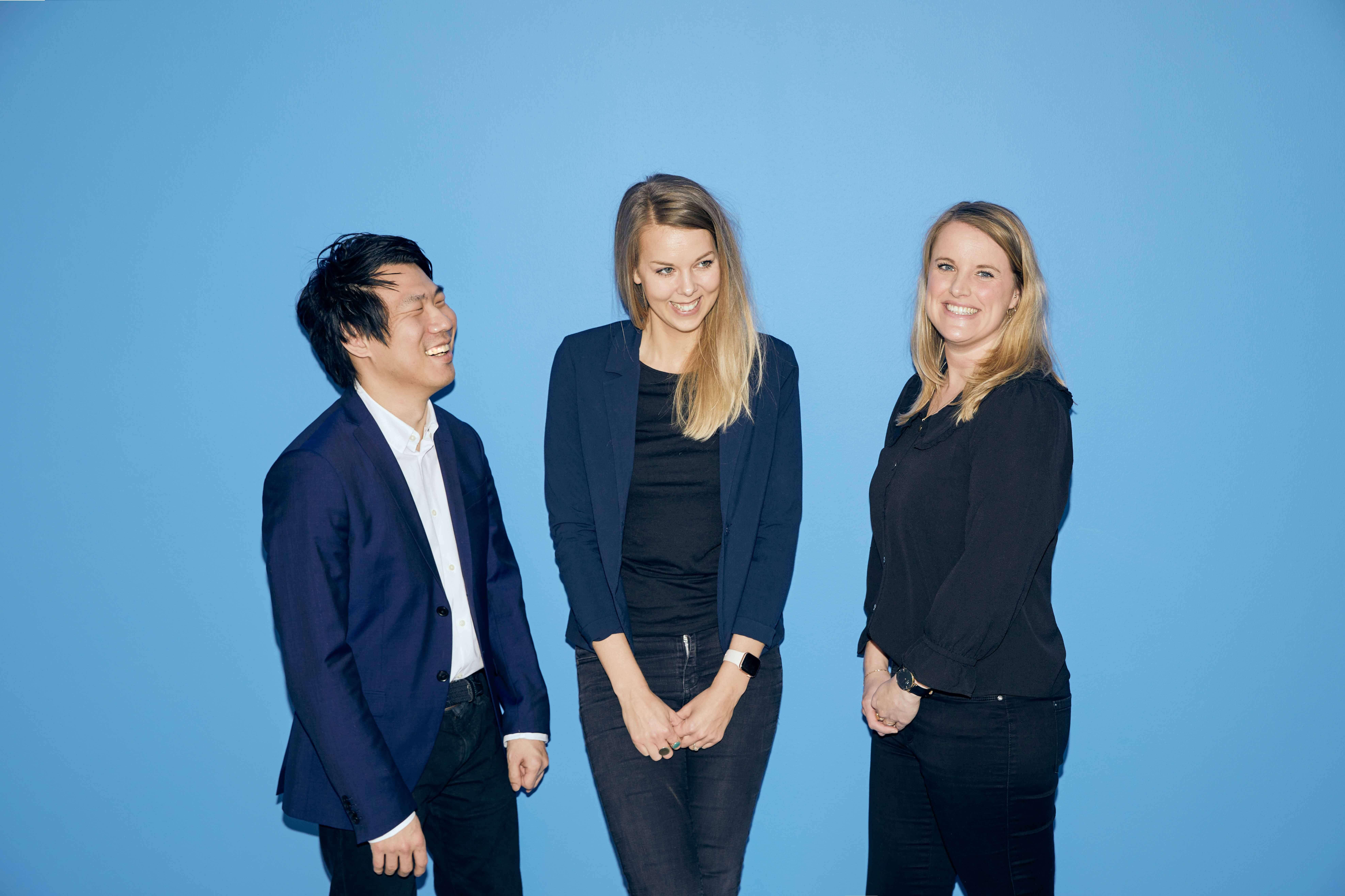 Et billede af Jacob Nossell til venstre, Signe Daugaard i midten og Katrine Larsen til højre. De stå foran en blå væg