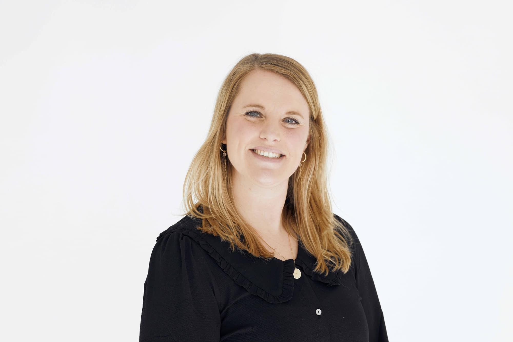Et billede af Katrine Larsen foran en hvid væg