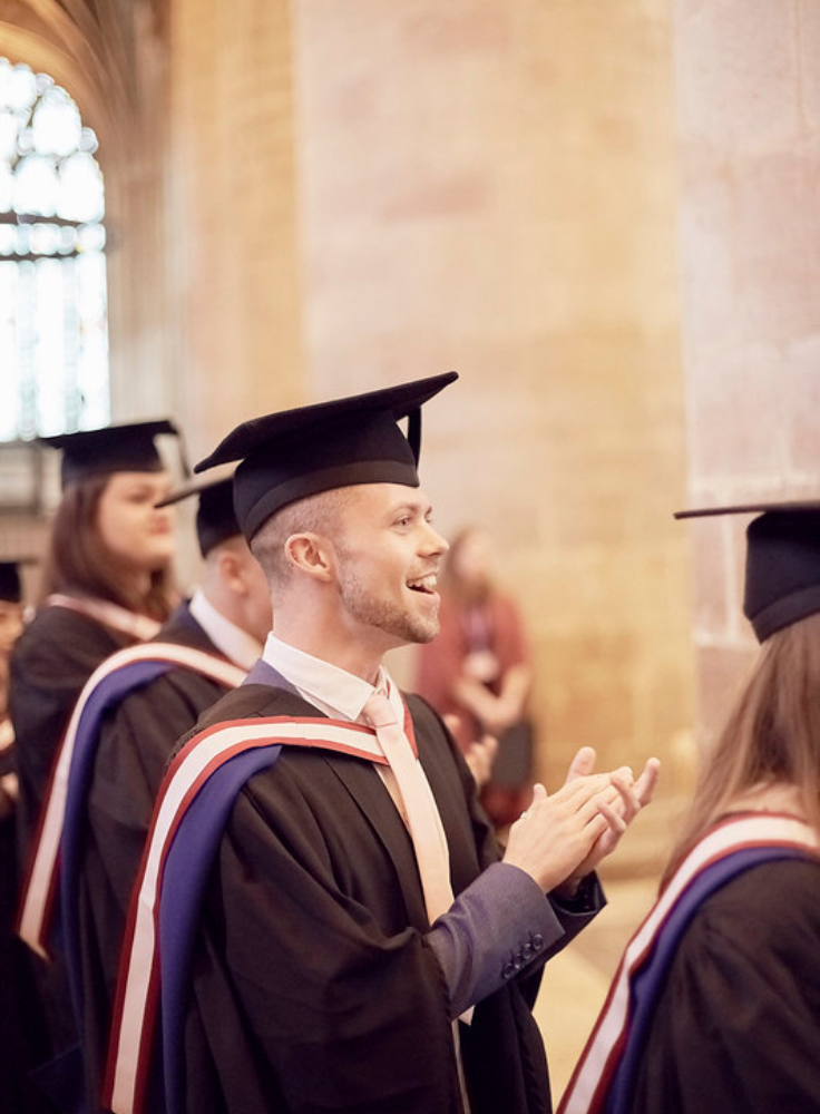 A six foot male stands clapping in a gothic cathedral dressed in a graduation gown, the man has a happy smiling expression and is amongst his peers celebrating their graduation event.