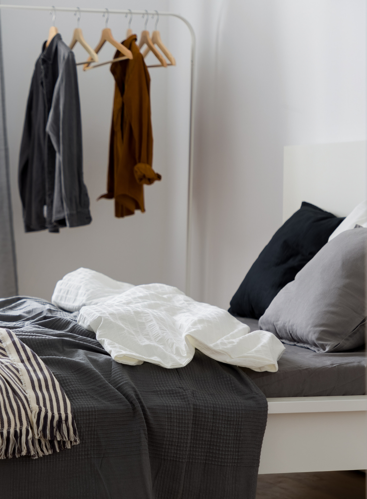 A halls of residence bedroom, centre is messy bed with a grey duvet and white pillows. In the background is a free standing wardrobe with two coats on.