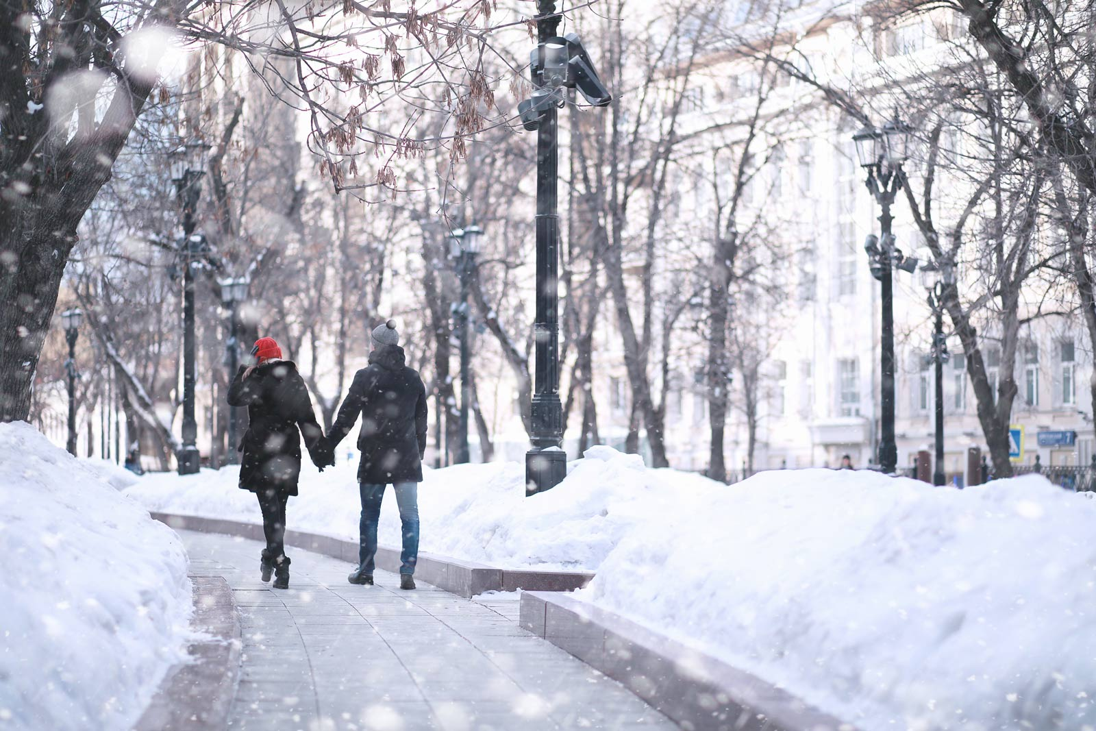 Two people holding hands walking through a park in the winter.
