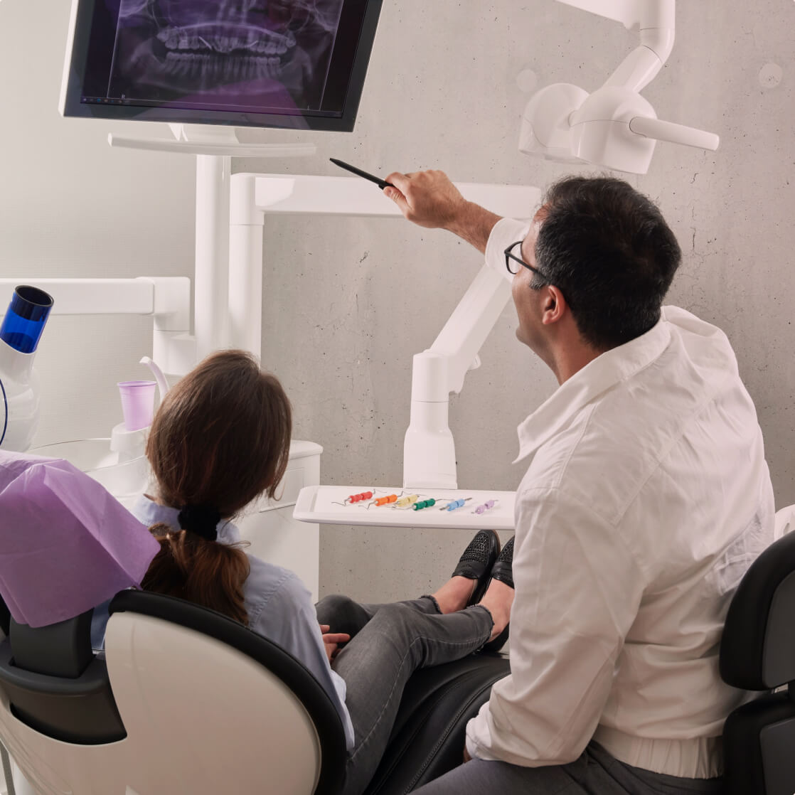 Dentist shows patient something on a monitor