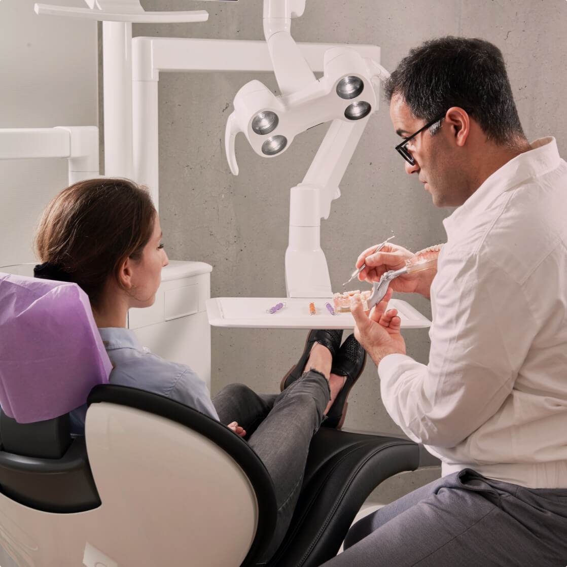 Dentist shows patient something on a model