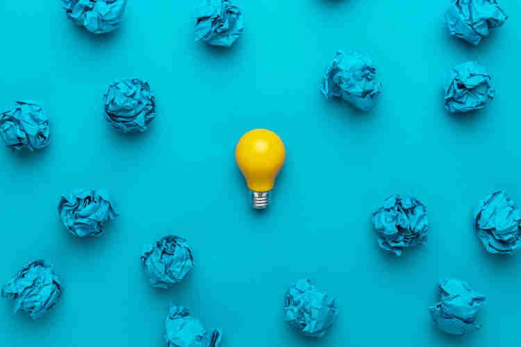 lâmpada de ideia se destacando em um fundo azul