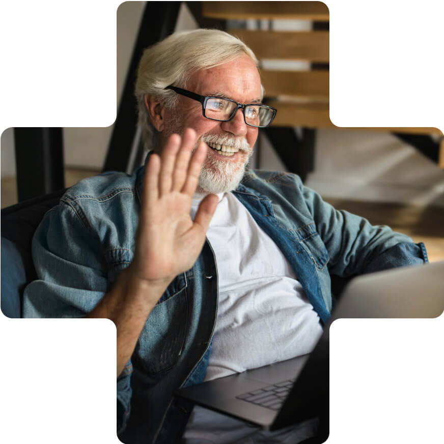 An older man waving hello to a user on a video conference on his computer