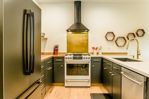Kitchen with fridge, range and smoke hood