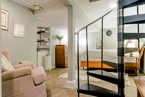 Spiral stairway down to basement room in Airbnb