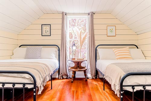 Twin beds in bedroom on second floor with bright window