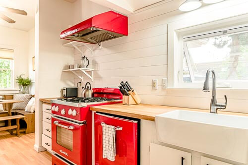 Kitchen entry with red appliances and wood countertops