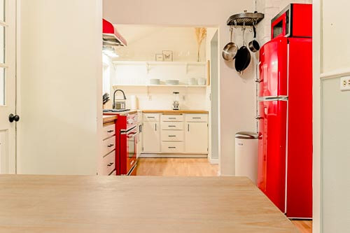Kitchen with red appliances from breakfast nook