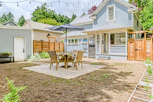 Backyard of Sellwood home with dining table