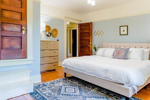 Bedroom with stairway to closet and wooden dresser