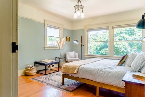 Bedroom with bright windows and blue paint