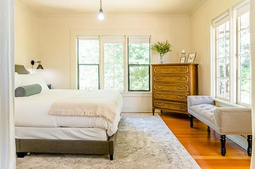 Bedroom with yellow paint and bright windows in NE Portland home