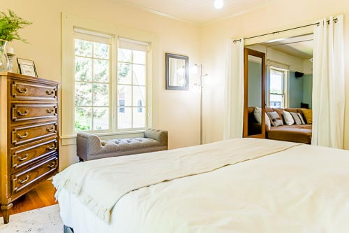 Bright warm bedroom with wooden dresser on second floor of home