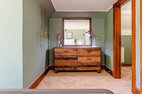 Dresser in third floor bedroom with green paint on walls