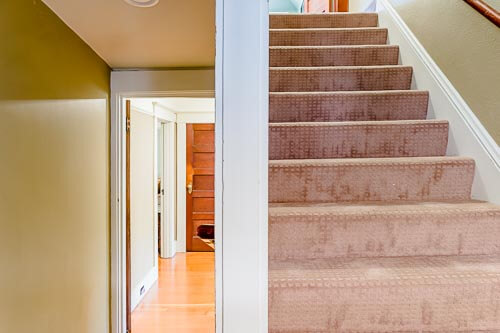 Carpeted stairs leading to third floor  of home