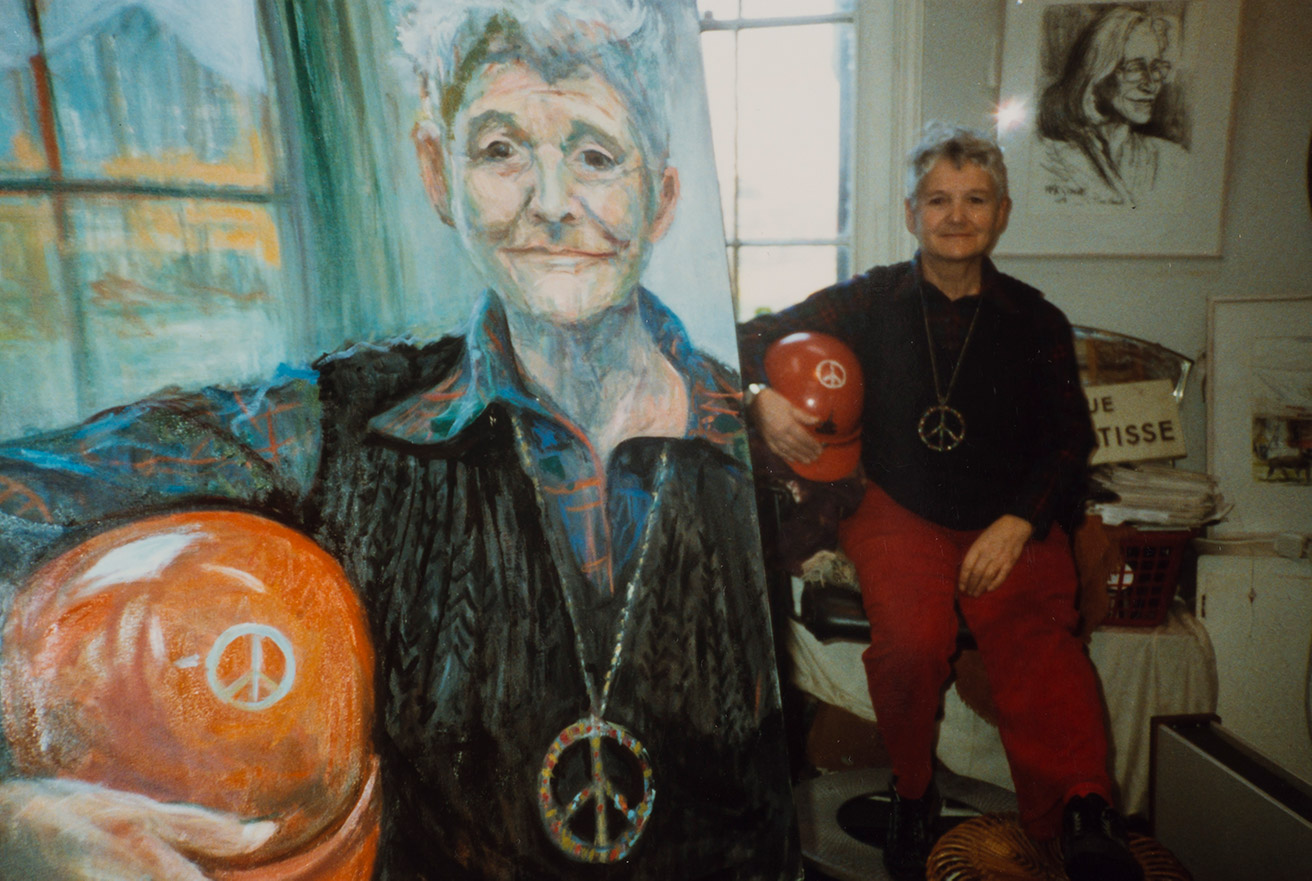 A painting of Pat Arrowsmith, with Pat sat beside it