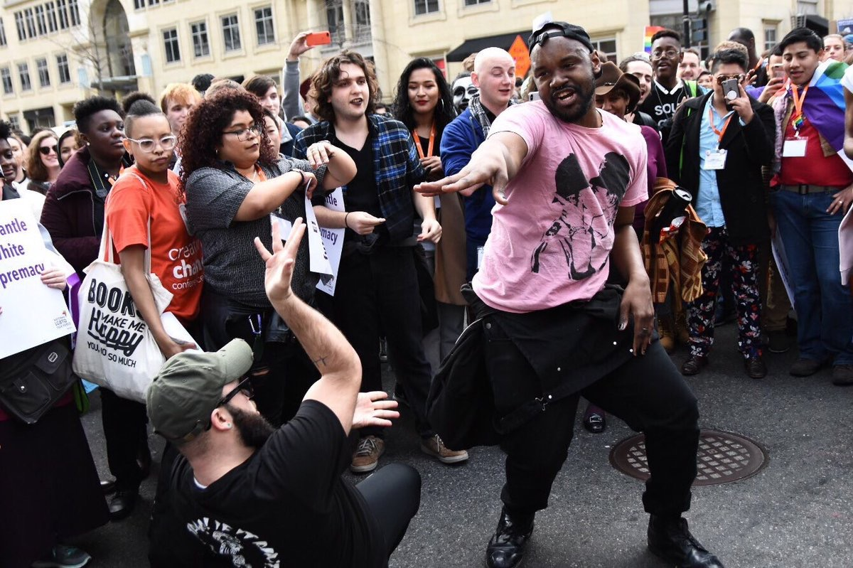 A man dancing in the street in a pink t-shirt