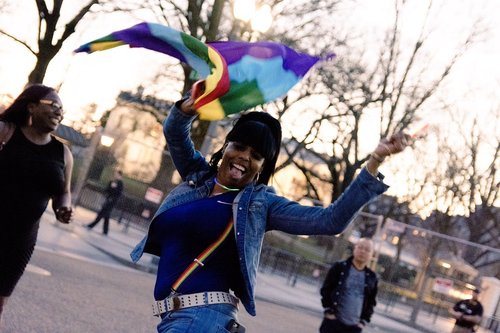 A woman dancing in the street with a Pride flag