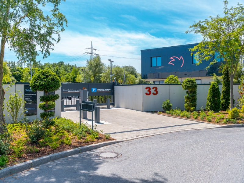 Die Auffahrt zu Grundstück der Stahlraum GmbH im Sonnenschein.