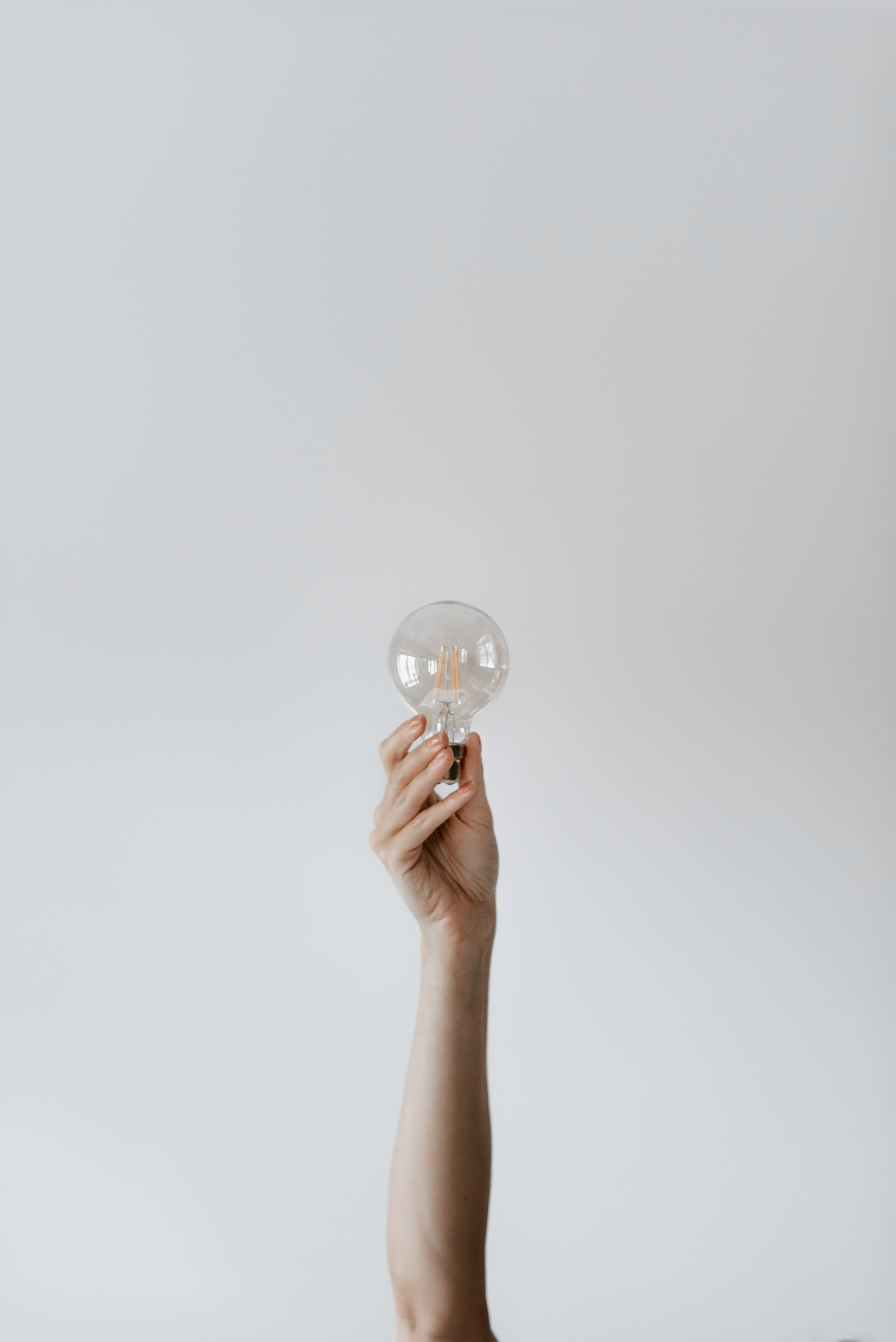 Image of a woman's arm holding up a lightbulb, on a white background