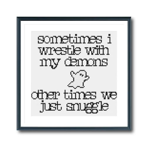 """A black and white cross-stitch with a little ghost in the middle that reads """"sometimes i wrestle with my demons other times we just snuggle"""""""