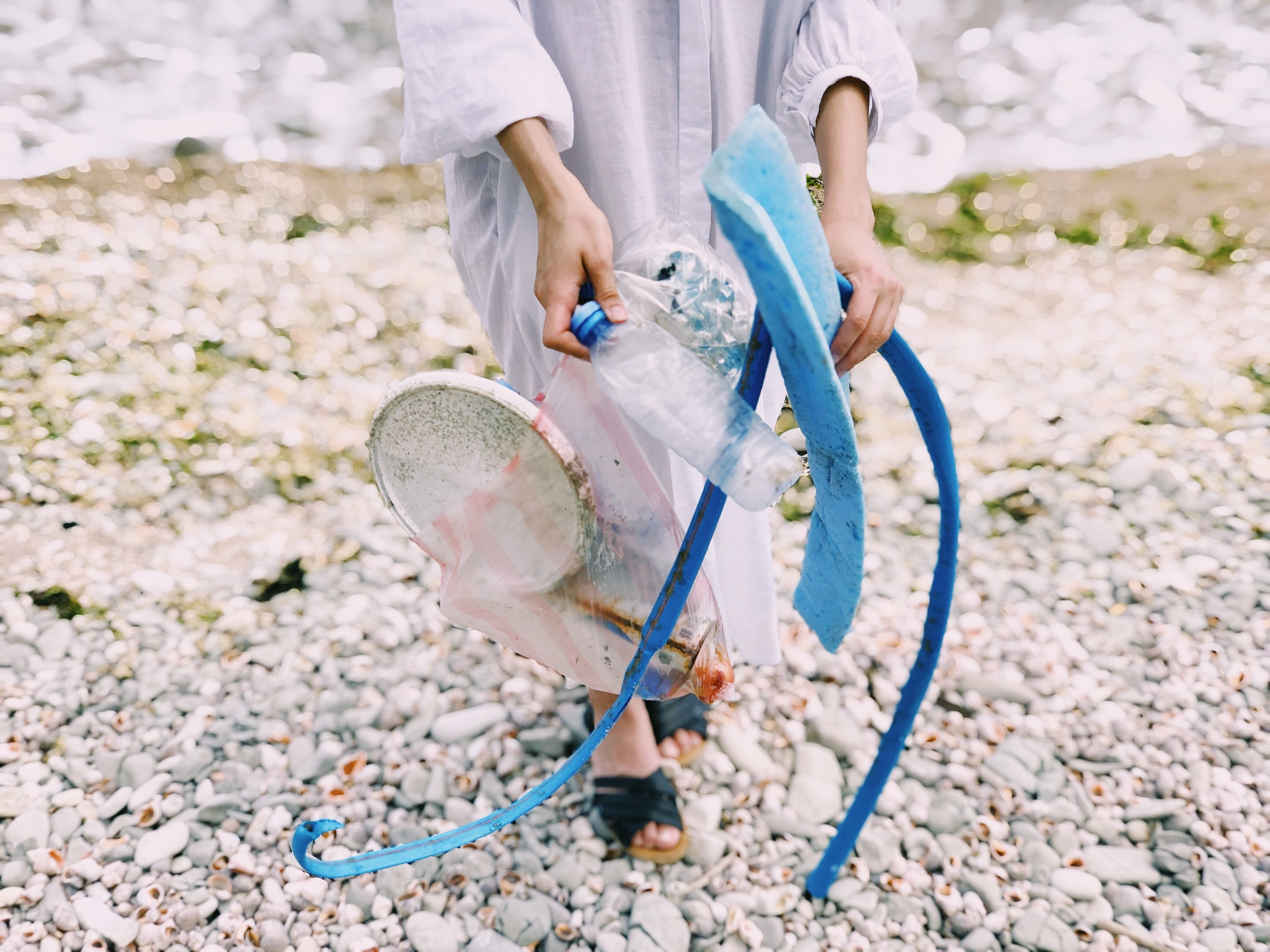 Photo of a woman on a beach holding litter she has collected.