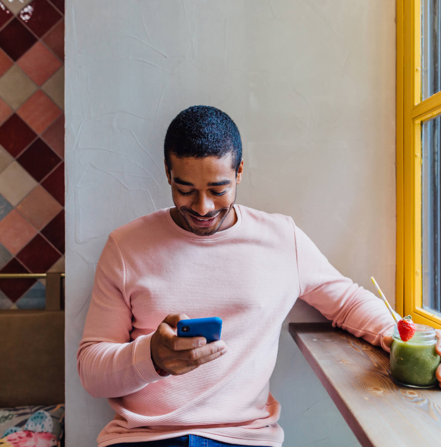 Guy in a pink shirt smiling at his phone
