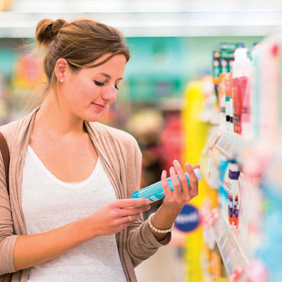 The point of contact, lady looking at a product on a shop shelf. Image from unsplash.com