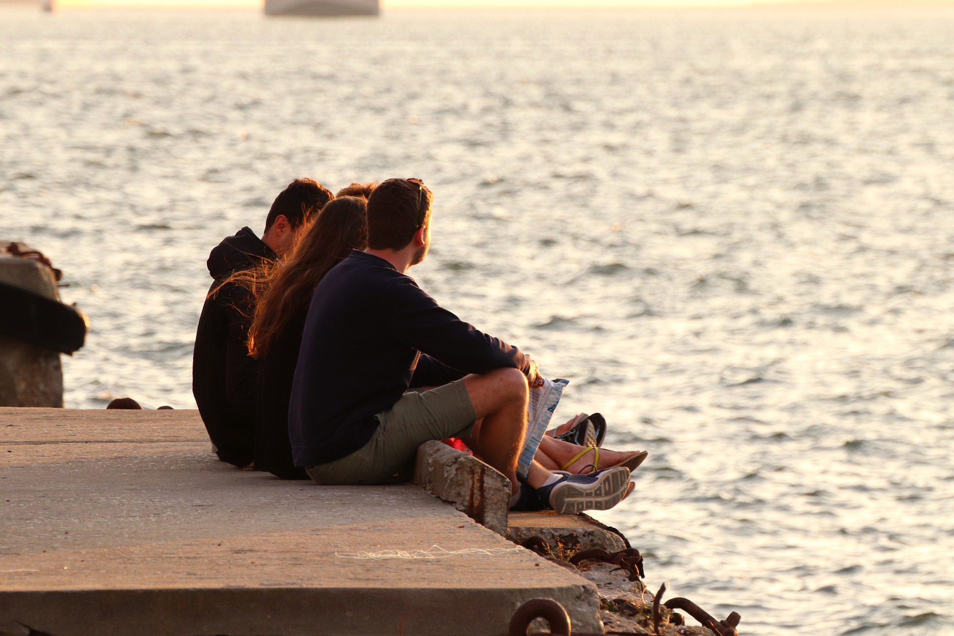 Young adults on lake pier.