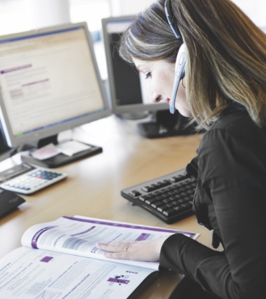 femme avec casque audio devant écran d'ordinateur et papier sur son bureau