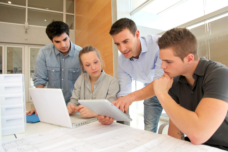 4 personnages qui discutent devant un écran - formation formateur