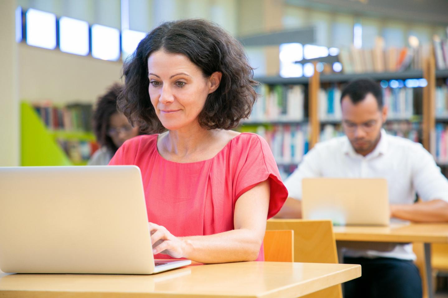2 personnages à la bibliothèque devant leur écran d'ordinateur