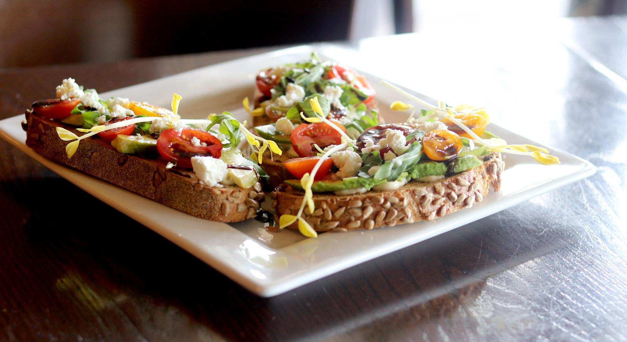 Avocado Toast | Avocado, Sangria Tomatoes, Arugula, Goat Cheese, Balsamic Glaze, Artisan Cranberry Bread