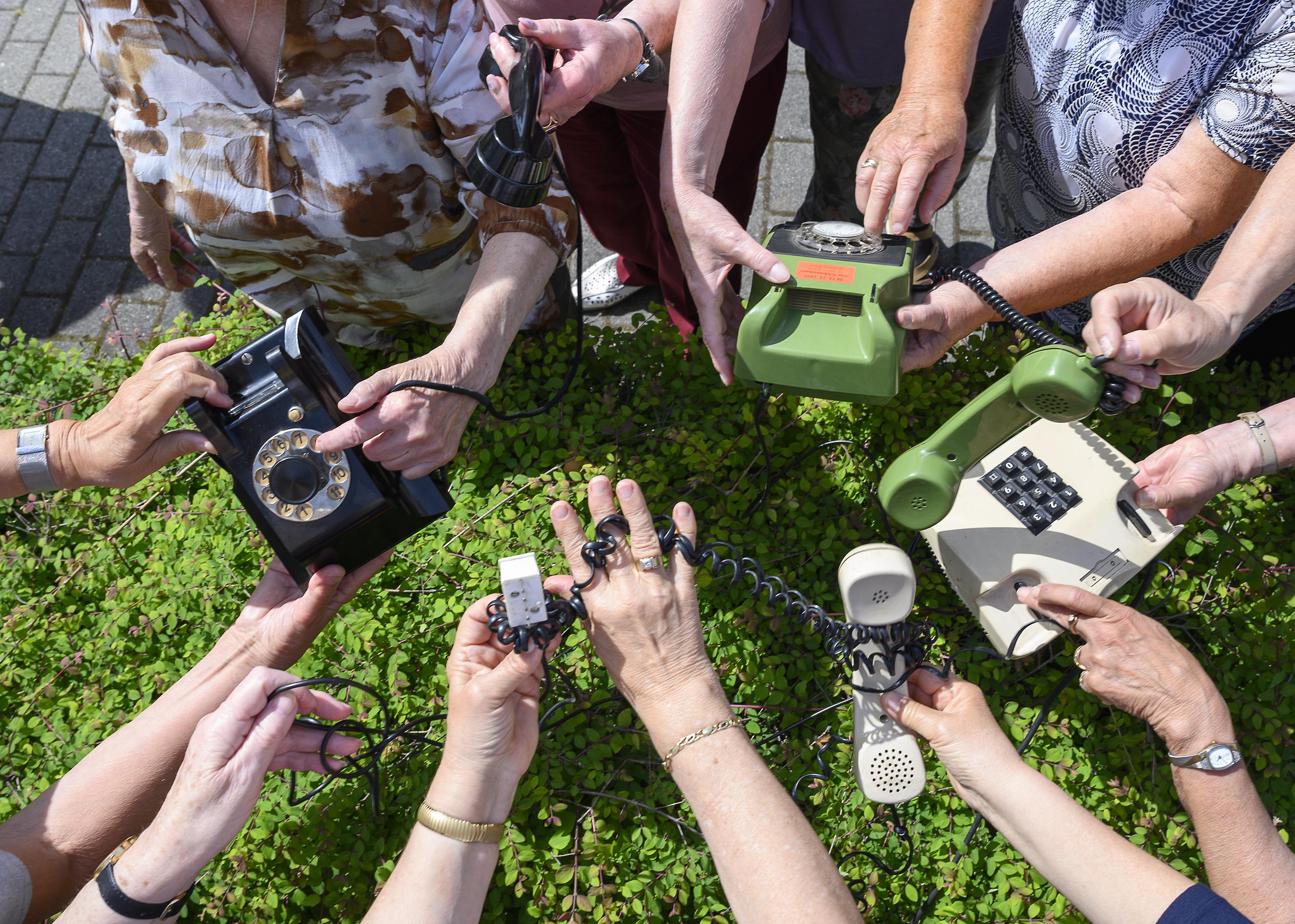 Viele unterschiedliche Hände greifen nach alten Wählscheibentelefonen auf einer grünen Hecke.