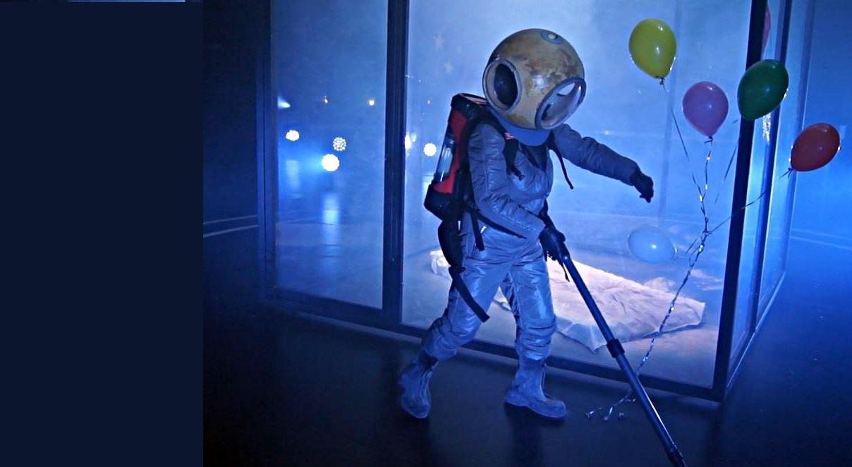 Astronaut mit Staubsauger auf dem Rücken vor einem Glascontainer, in dem eine Matratze liegt. Daneben bunte Luftballons.
