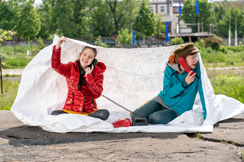 Zwei weibliche Personen unterschiedlichen Alters telefonieren an Wählscheibentelefonen im öffentlichen Raum auf weißer Decke sitzend.